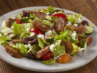 plate of mediterranian style salad with Johnsonville Foodservice Hot Italian Sausage Links, greens, olives, and tomatoes
