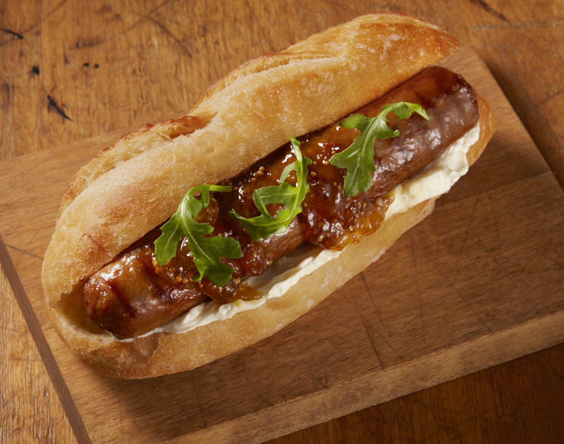 Johnsonville Foodservice grilled All-Day Sausage featuring French Toast Sausage flavor served in a bun with glaze and garnish